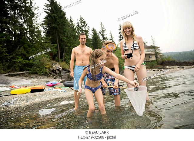 Family fishing with net in lake
