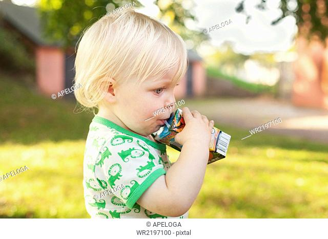 Side view of cute baby boy drinking from juice box at park