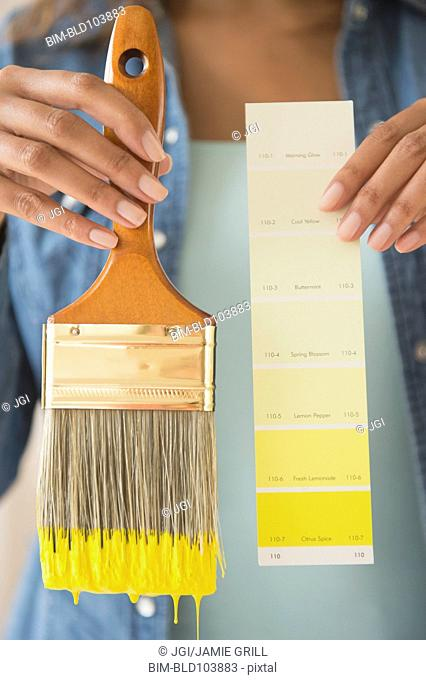 Cape Verdean woman holding color swatch and paintbrush