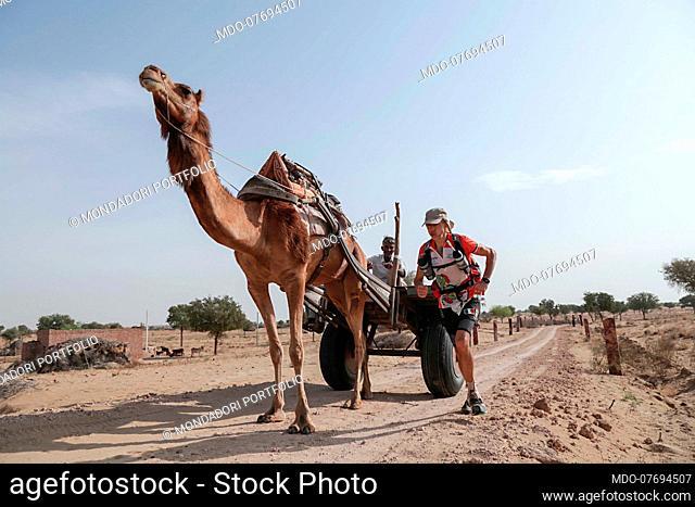 Ultramarathon Project. A runner overpasses a local farmer and his camel. Thar Desert (India), April 11th 2018