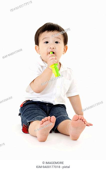 Baby boy sitting on the ground and playing toy