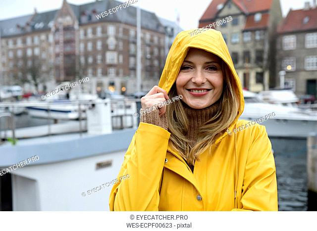 Denmark, Copenhagen, portrait of happy woman at city harbour in rainy weather