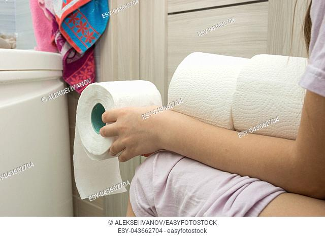 The girl is sitting on the toilet and holding a few rolls of toilet paper