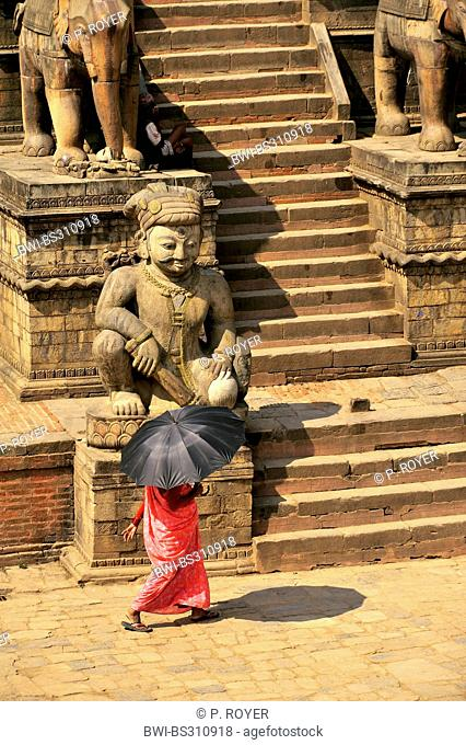 woman with an umbrella serving as a sunshade crossing the Bhaktapur Durbar Square at the royal palace, Nepal, Bhaktapur