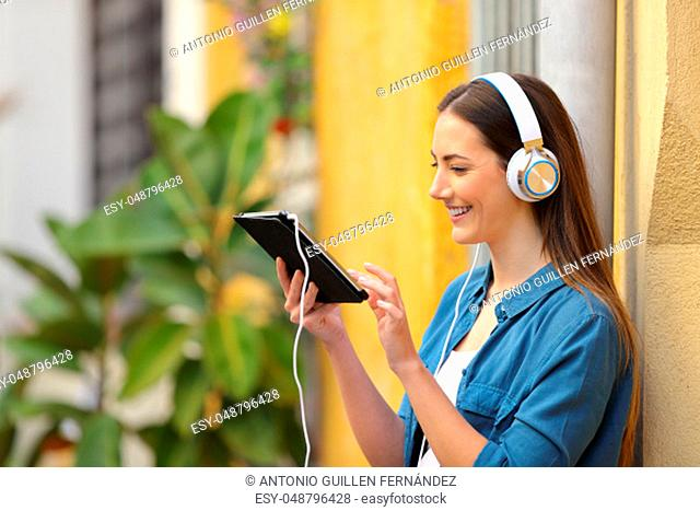 Happy girl listening and watching tablet online content in the street