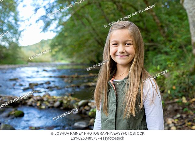 Young girl in a green vest posing for a lifestyle portrait outdoors along the banks of the McKenzie River in Oregon