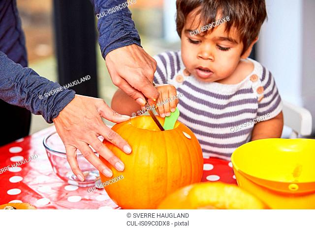 Boy helping mother gut pumpkin in kitchen