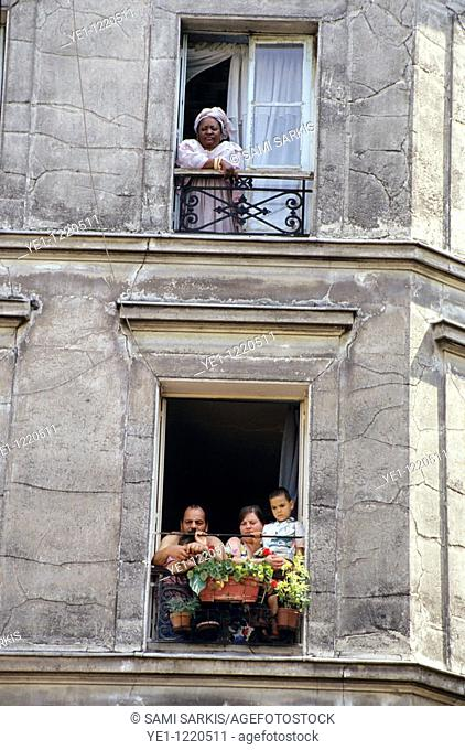 Neighbours looking out their windows of apartment buildings in the 18th arrondissement, Paris, France