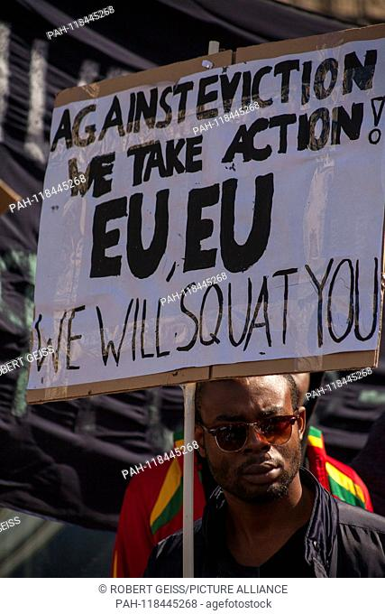 """African migrant during rally against racism. Shield """"""""Against deportations We will get active EU we will occupy you"""""""". 16.03.2019 