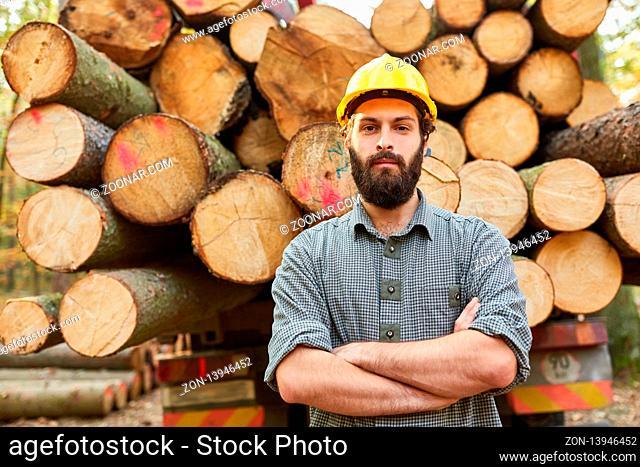 Stolzer Waldarbeiter mit verschränkten Armen vor einem Langholzwagen