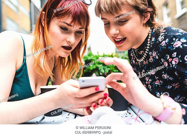 Two young women at sidewalk cafe table looking at smartphone