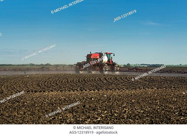 Crop sprayer in clean soil field with blue sky and clouds, East of Calgary; Alberta, Canada