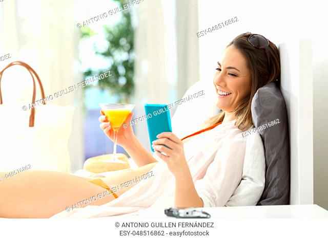 Side view portrait of a woman enjoying summer vacations using a smart phone on a bed of an hotel room
