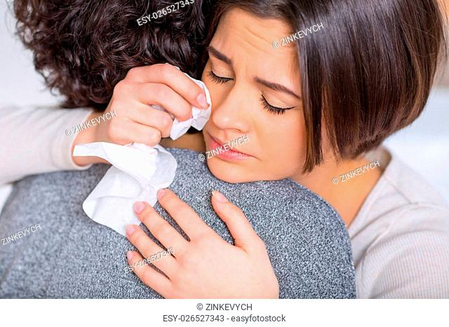 Feeling sad. Young nice-looking woman is hugging her sister while weeping sadly