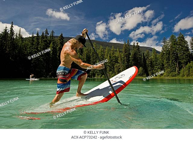 A professional paddle boarder practises tricks while enjoying the tropical waters of Johnson Lake, North of Kamloops in the Thompson Okanagan region of British...
