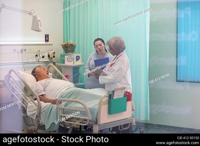 Doctors making rounds, talking with patient in hospital room