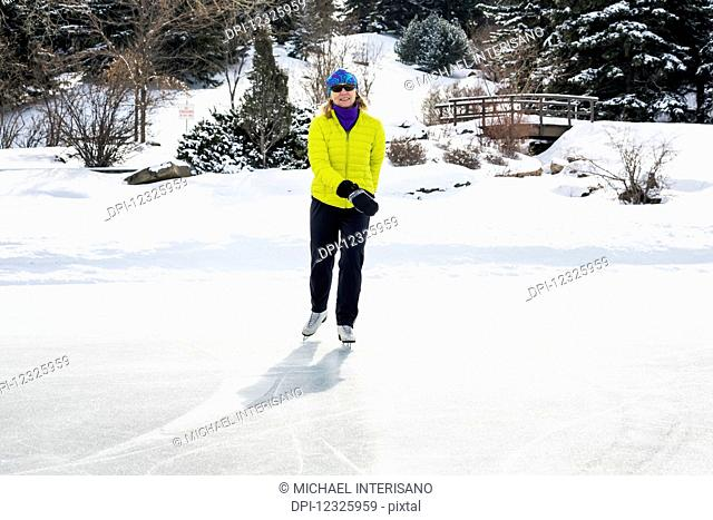 Woman skating on frozen pond with snow covered wooden bridge in the background; Calgary, Alberta, Canada