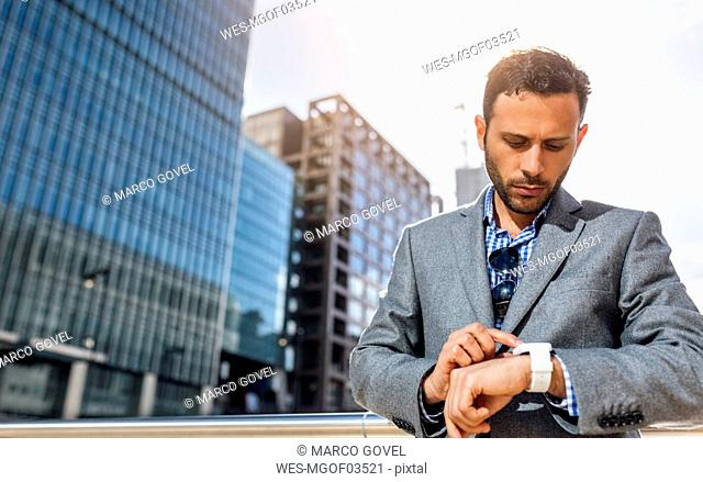 Businessman checking the time in the city
