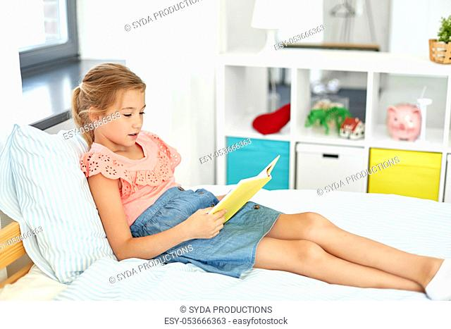 happy little girl reading book at home