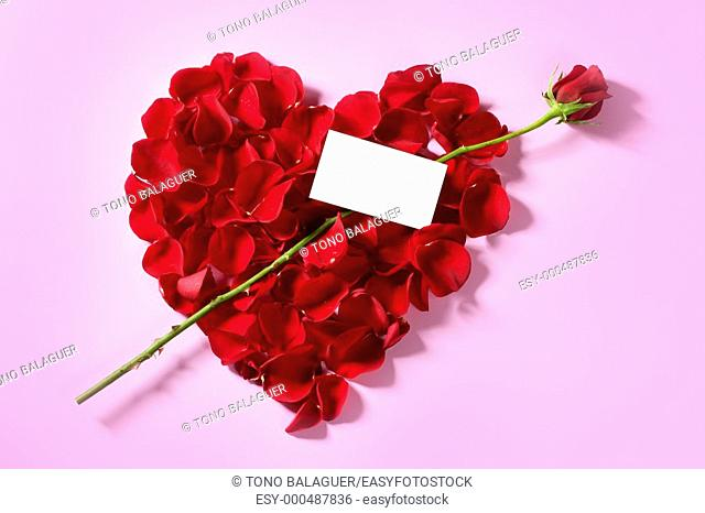 Red rose petals in heart shape with a copy space blank note