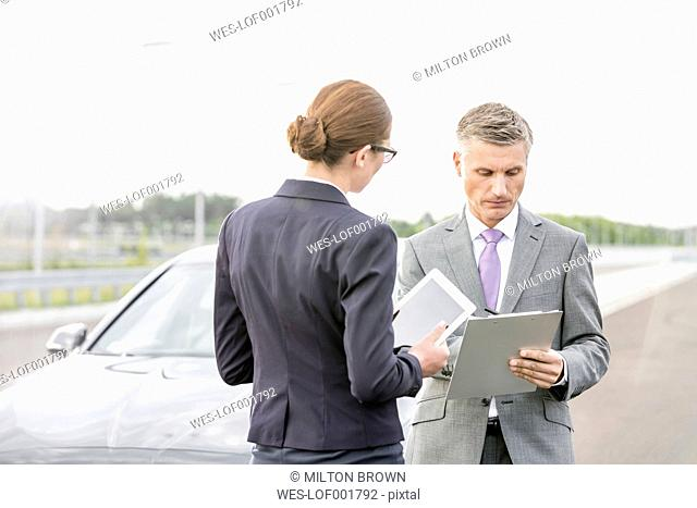 Businessman and businesswoman with clipboard and digital tablet at a car