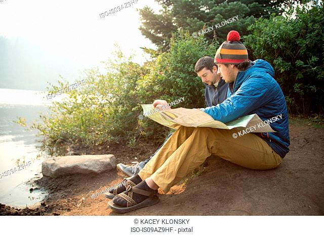 Two young male hikers reading map by lake, Mount Hood National Forest, Oregon, USA