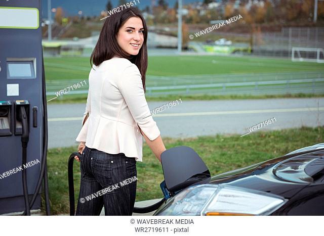 Portrait of beautiful woman charging electric car