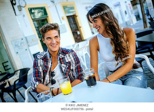Happy young couple in love sitting at sidewalk cafe