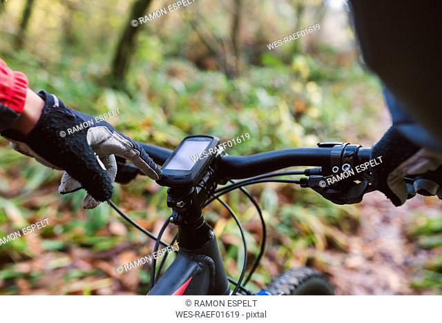 Mountain biker using GPS of his bike, close up