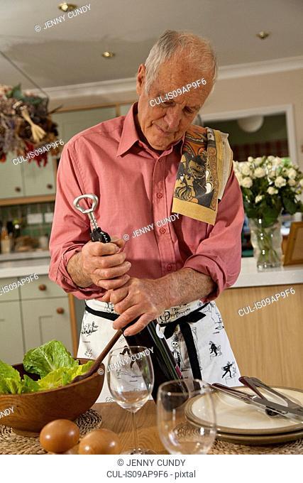 Senior man opening bottle of wine
