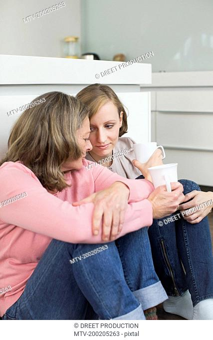 Mother and adult daughter side by side with cup of coffee