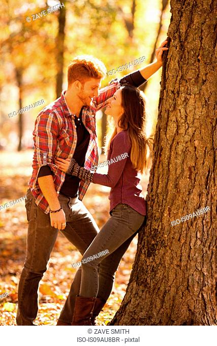 Romantic young couple leaning against tree in autumn forest