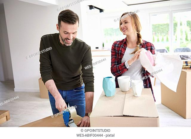 Couple moving house packing and taping cardboard boxes