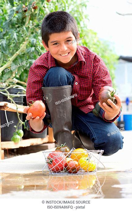 Boy crouching holding ripe tomatoes