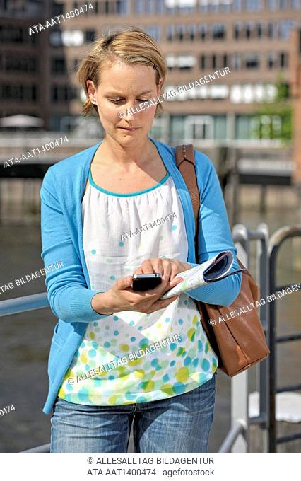 Tourist with a city map and smartphone