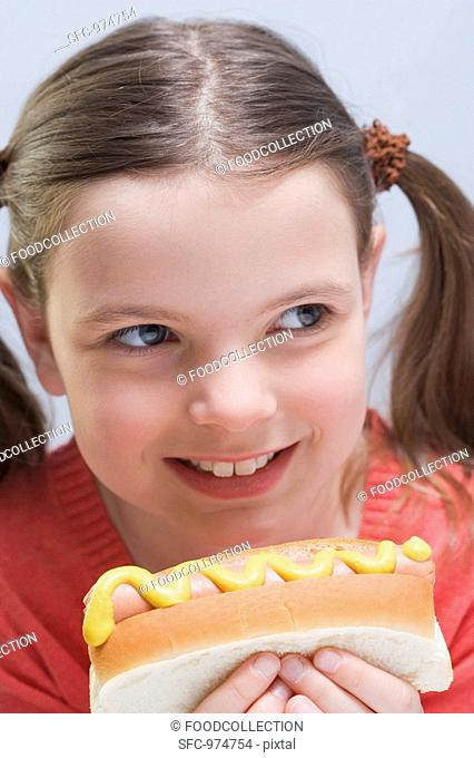 Smiling girl holding hot dog with mustard