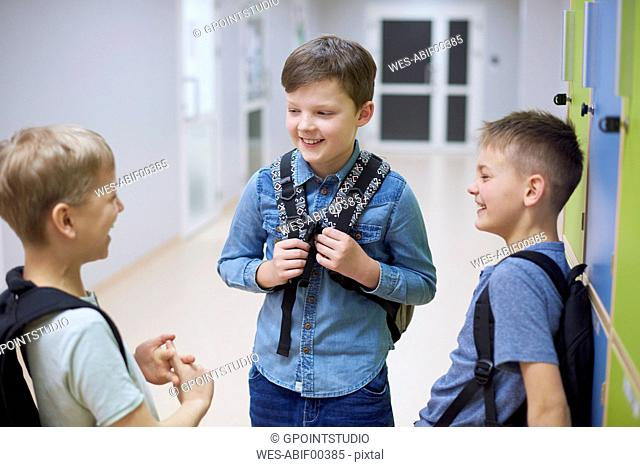 Happy pupils talking at lockers in school