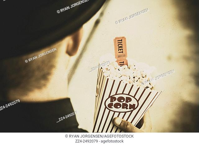 Old toned horizontal image of an old-fashioned man holding admit one movie ticket and stripe pop corn container. Walk down memory lane