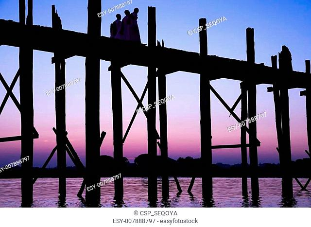 Bridge U-Bein teak bridge is the longest. Sunset with silhouettes of people unrecognizable