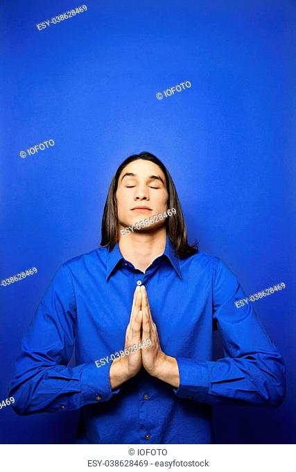 Portrait of Asian-American teen boy with palms pressed together in prayer position standing against blue background