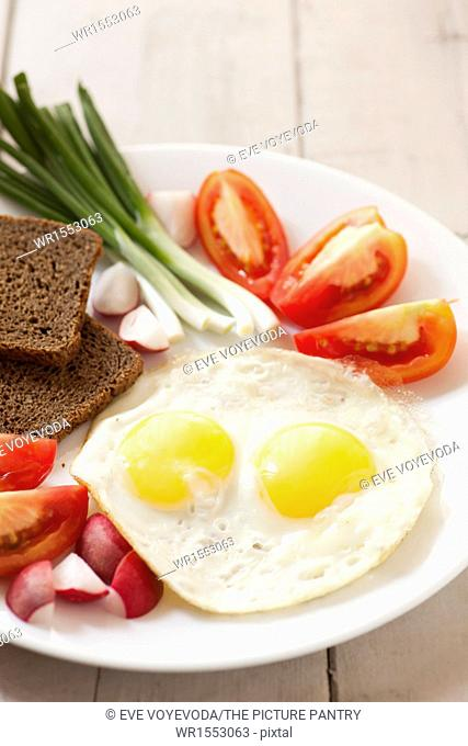 Two fried eggs with yellow yolks and vegetables