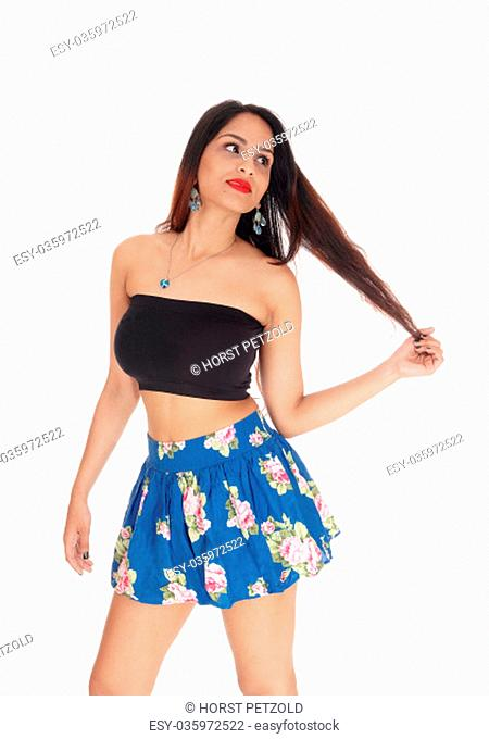 A gorgeous young woman standing in a blue short skirt and black.top, looking away, isolated for white background