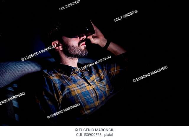 Bearded mid adult man sitting on sofa in darkness looking up through virtual reality headset