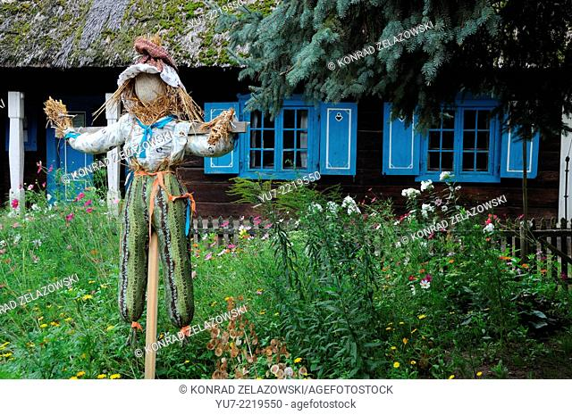 Scarecrow in front of very old wooden hut witch thatched roof