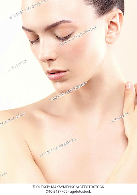 Closeup face beauty portrait of a young woman with closed eyes with natural makeup and clean skin