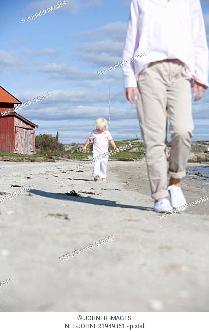 Mother with son walking on beach, Vastkusten, Sweden