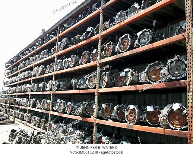 Used automotive transmissions for resale on a large outdoor rack at a salvage yard in Spokane, Washington, USA
