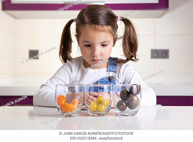 Little girl observing cherry tomatoes varieties colors. Education on healthy nutrition for children