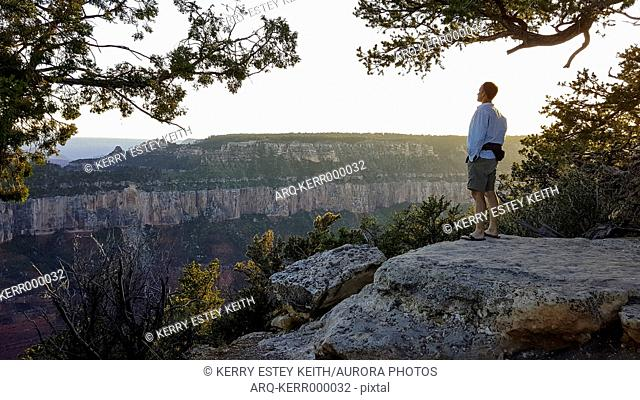 Lone man standing and looking at view on North Rim of Grand Canyon, Arizona, USA