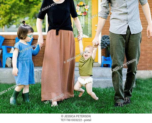 Parents with daughters (2-3, 12-17 months) standing on grass
